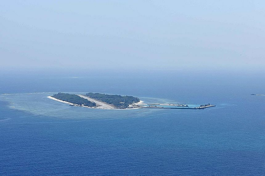 A Taiwanese coast guard (top) securing a military transport plane on Itu Aba (above), which the Taiwanese call Taiping.If the outcrop is considered an island, the Philippine's case will be out of the tribunal's jurisdiction.