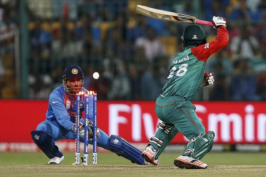 """India captain Mahendra Singh Dhoni stumping Bangladesh opener Tamim Iqbal in their World Twenty20 Group 2 cricket match in Bangalore on Wednesday. He described his team's one-run win as being able to """"manage chaos"""", but hosts India must beat Australi"""