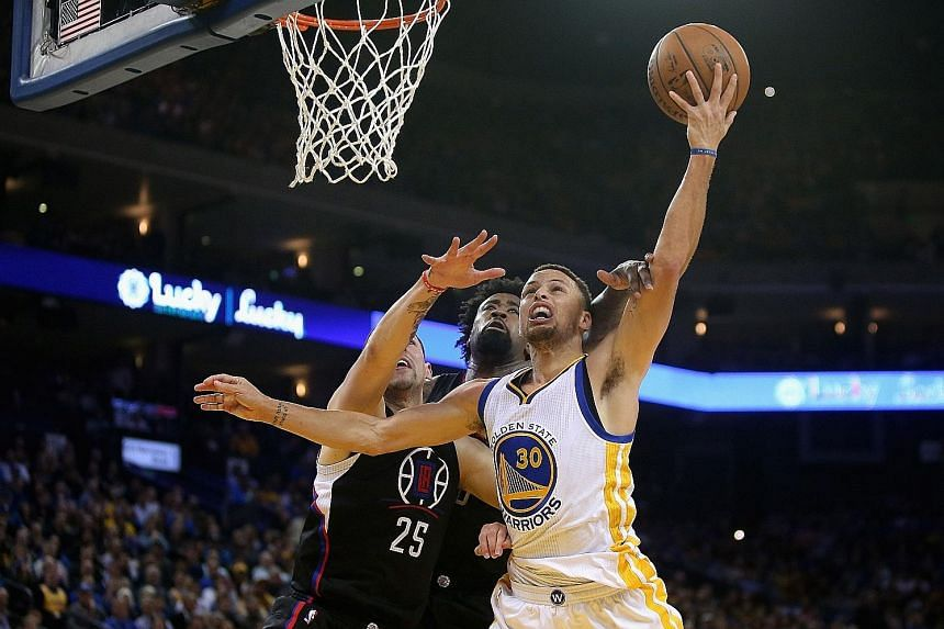 Stephen Curry (No. 30) of the Golden State Warriors going up for a shot against Austin Rivers (No. 25) and DeAndre Jordan of the Los Angeles Clippers on Wednesday. The Warriors' 114-98 win sealed a 4-0 season-series sweep against the Clippers.