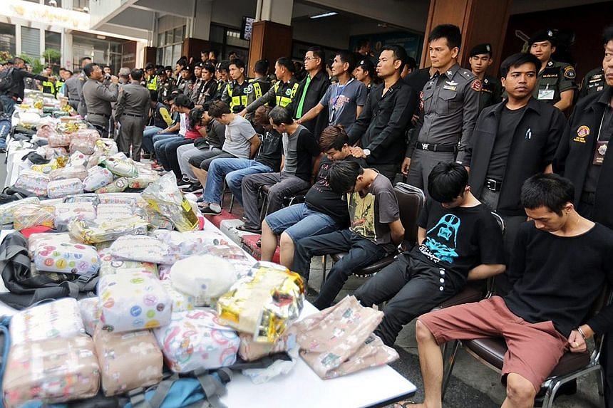 Malaysians alleged to be members of a drug-trafficking gang lined up next to bags of heroin and methamphetamine. They were arrested for trying to smuggle the drugs by train from Thailand into the Malaysian town of Butterworth.
