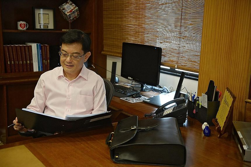 Finance Minister Heng Swee Keat, in his office yesterday, prior to delivering his maiden Budget. Analysts said the Budget was a prudent one, with Mr Heng balancing short-term concerns and long-term challenges. The Government pledged to support worker
