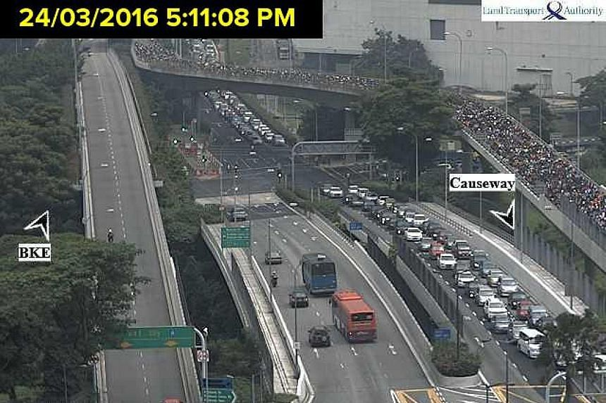 Traffic was already heavy at the Woodlands Checkpoint yesterday at around 5pm (above left) and the queues remained long as night fell.
