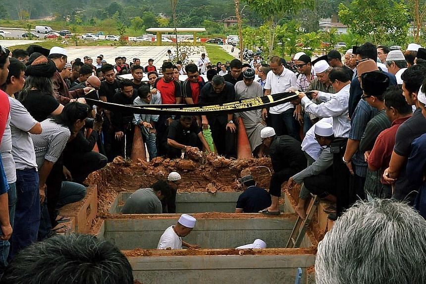 The funerals of SMRT trainees Muhammad Asyraf and Nasrulhudin at the Muslim cemetery in Lim Chu Kang on Wednesday. The two men were killed on Tuesday when they were hit by an oncoming train.