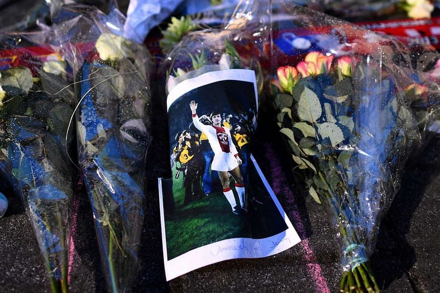 A man lays flowers near the statue of Johan Cruyff in front the Olympic Stadium, in Amsterdam, on March 24, 2016.