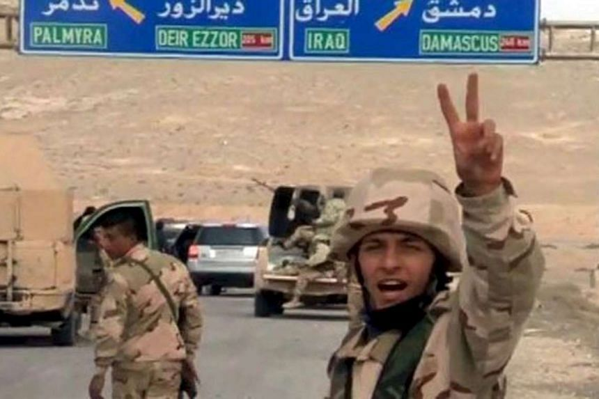 Syrian forces gesture as they advance into the historic city of Palmyra in this picture provided by Sana on March 24, 2016.