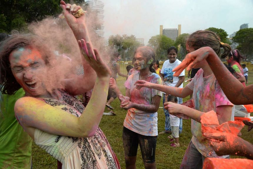 Participants throw coloured powder at each other during Holi Mela 2016 at the open field along Tanjong Rhu View.