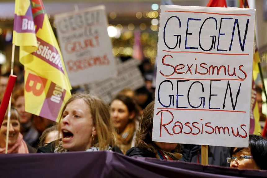 """Women hold a placard that reads """"Against Sexism - Against Racism"""" during a march in Cologne, Jan 5, 2016."""