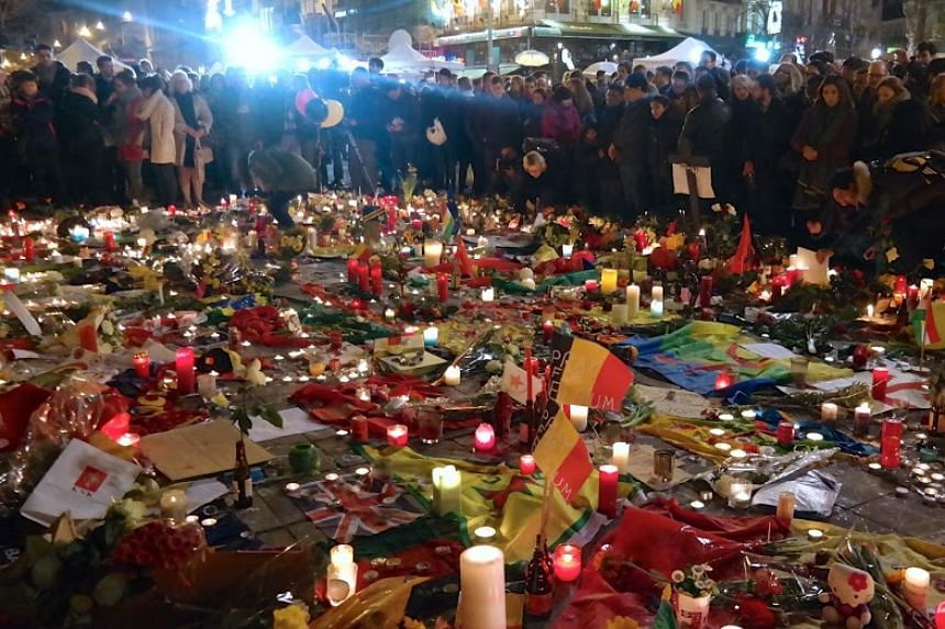 The square is covered in a sea of candles, flowers and Belgian flags.