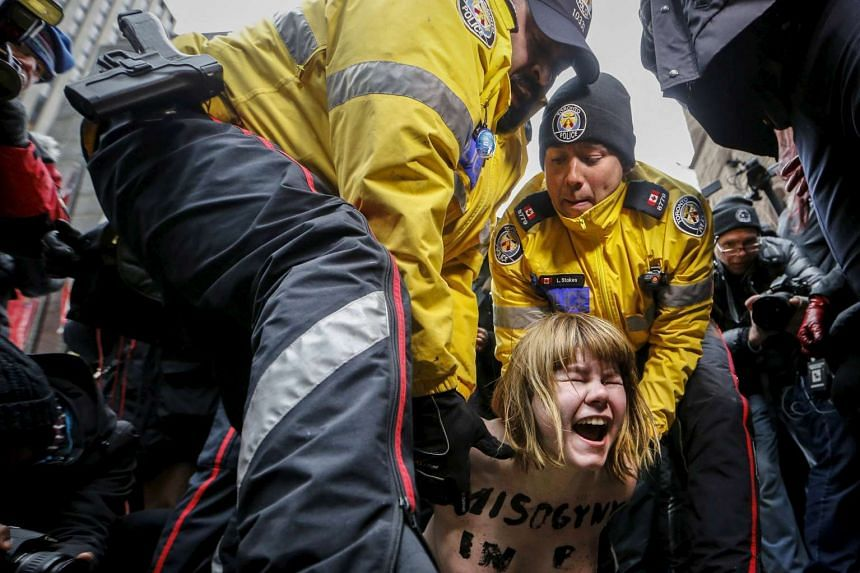 A shirtless protester is detained by police after an Ontario judge found Ghomeshi not guilty.