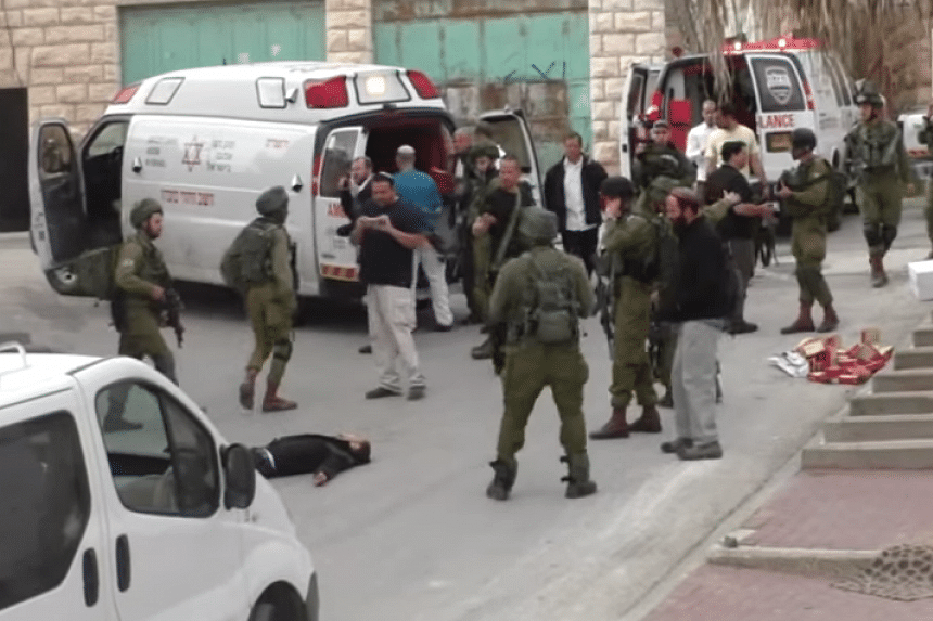The man lies on the ground surrounded by soldiers before being shot in the head, in a screenshot from the video posted online.
