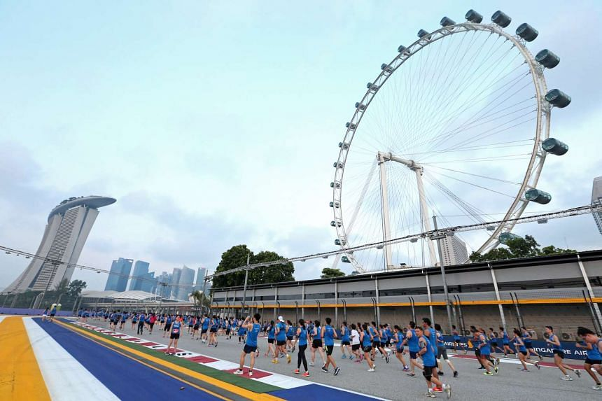 Runners making their way past the Singapore Flyer during the ST Run at the Hub in September 2014. Aspects of F1 will be woven into this year's ST Run in the City on May 22, and runners will stand to win tickets worth over $12,000 to the Singapore Gra