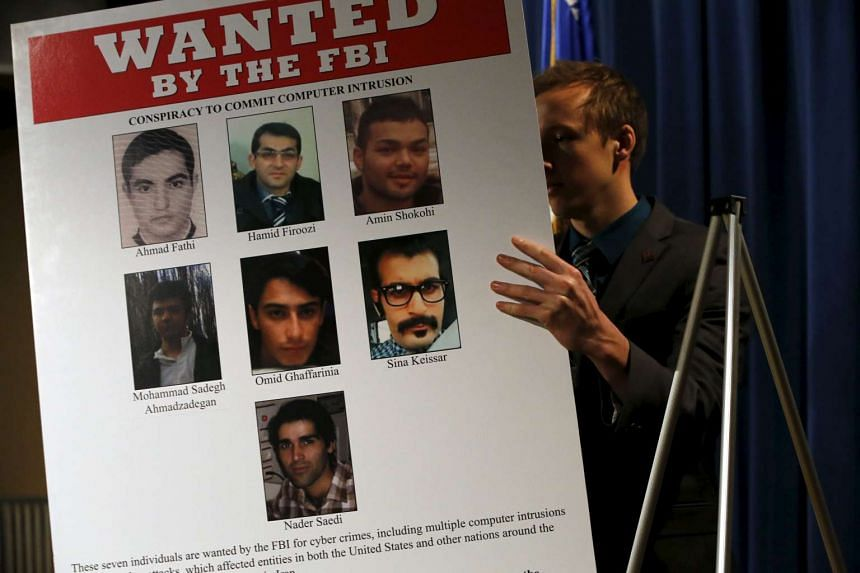 An aide unveils a wanted poster before US officials hold a news conference about the hacking.