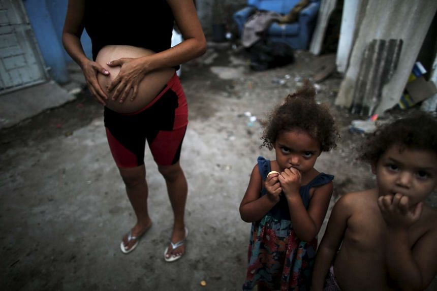 Patricia Araujo (left), 23, who is seven-months pregnant, stands next to children as they pose in front of their stilt house, a lake dwelling also known as palafitte or 'Palafito', in Recife, Brazil, on Feb 8, 2016.