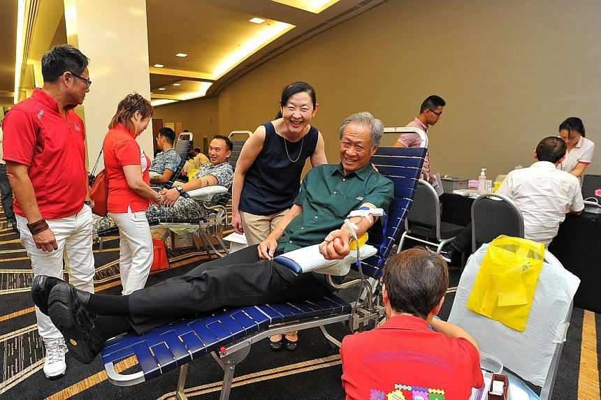 Dr Ng donating blood, with his wife, Professor Ivy Ng, standing by his side. Dr Ng was among the close to 100 people who participated yesterday in the inaugural Drops of Life blood drive by LoveSingapore at Suntec Singapore Convention and Exhibition