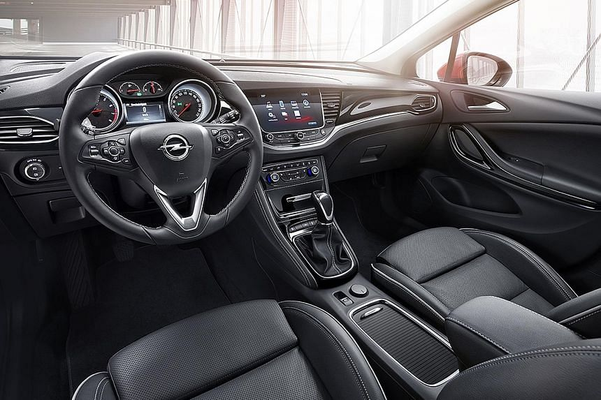 The Opel Astra Sports Tourer boasts a snazzy cockpit (below left) and a capacious boot (below).