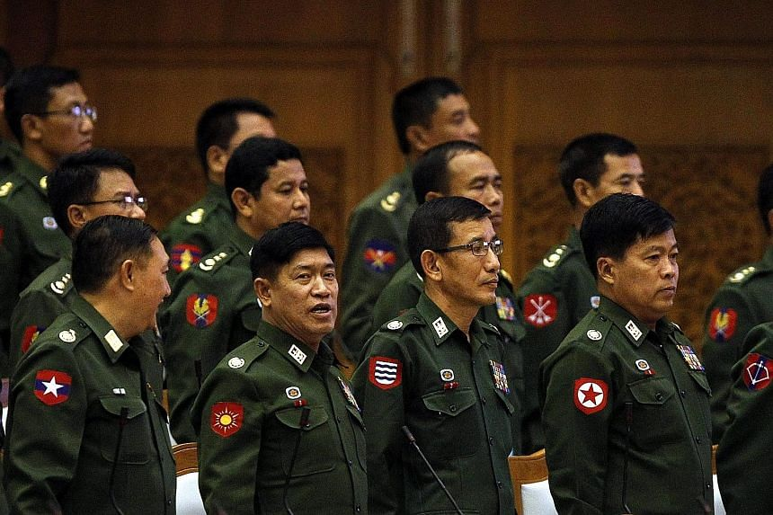 """Military representatives at a Parliament session in Naypyitaw. The military has climbed down to allow Myanmar's experiment with democracy, but this will be a """"firewalled"""" democracy."""