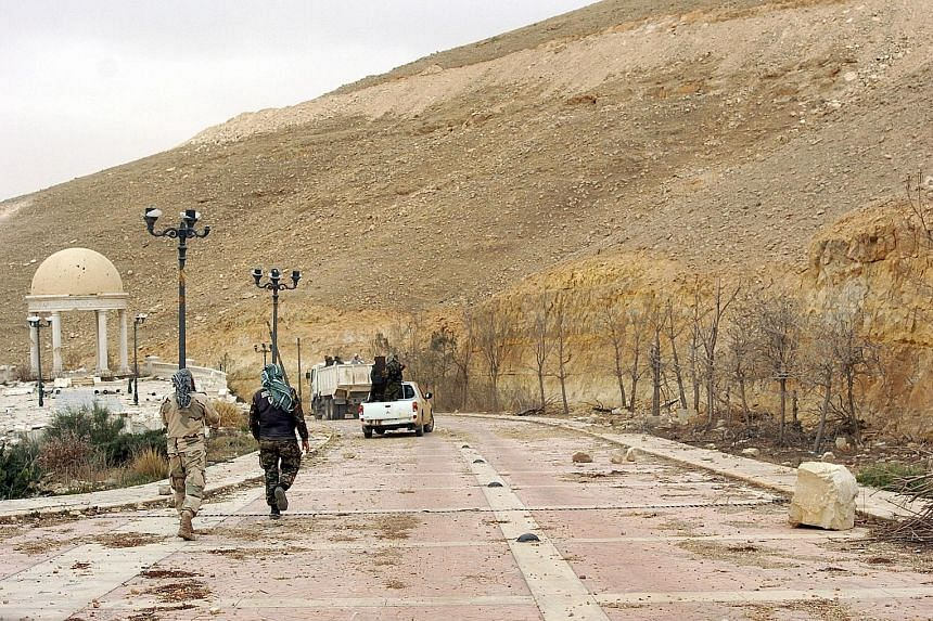 Syrian soldiers walking down a Palmyra street. A Russian officer was killed in combat near the city recently, suggesting the Kremlin has been more deeply engaged in the conflict than it has acknowledged.