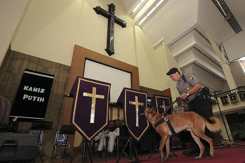 A police officer and his dog searching a church ahead of Easter celebrations in Surabaya, Java. Indonesia has intensified security at churches and other places this Easter weekend.