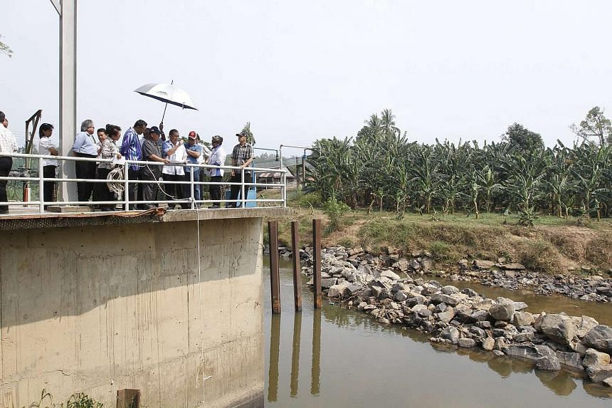 Mr Pairin (in grey) and government officers visiting a water treatment plant in Penampang, Sabah, on Thursday.