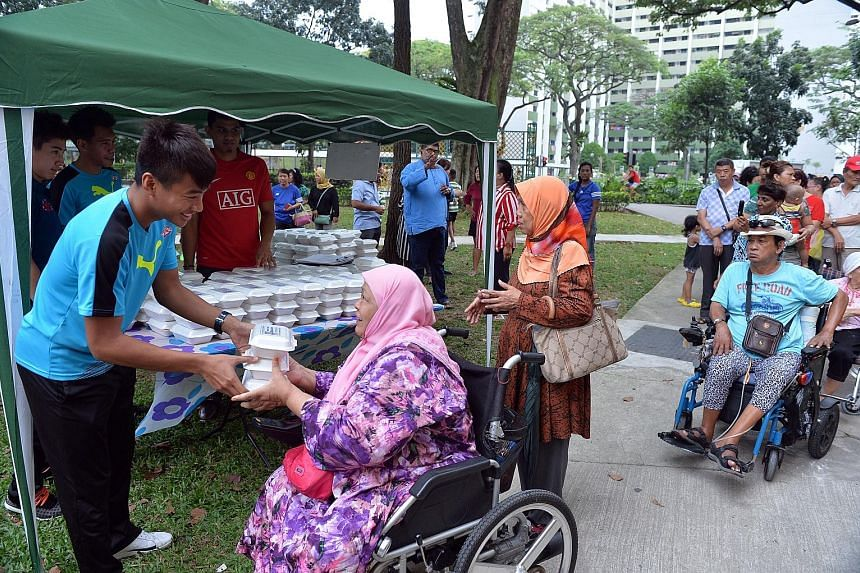 Home United FC player Sufianto Salleh helping to distribute packets of food to the elderly in Boon Lay Drive yesterday. The team players were acting in partnership with charity Free Food For All, which distributes halal meals to the elderly and under