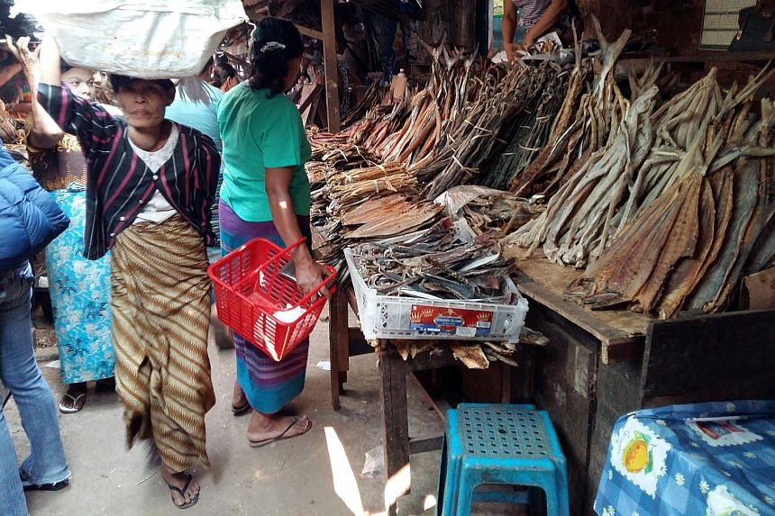 Mr Saw Hdaik Oo (above) is back home in Dawei, Myanmar, after 15 years in Thailand. He still works for his Thai boss, who is expanding the business to Dawei. A market (left) in Dawei.