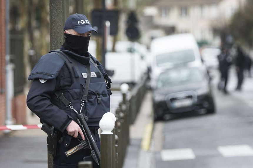 A police officer standing outside a building after an anti-terrorism operation in Argenteuil, near Paris, on March 25.