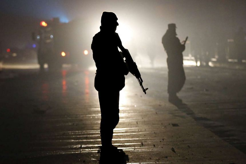 Afghan policemen stand guard after a suicide bomb attack near the Russian embassy in Kabul on Jan 20, 2016.