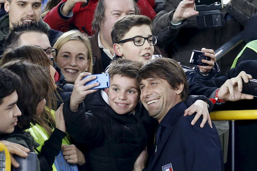 Meanwhile, Italy coach (above ) Antonio Conte (posing with a fan) is slated to take the reins at Chelsea after leading the Italians at Euro 2016, with an officer from the Premier League club spotted in close quarters with the Italian's contingent at the m