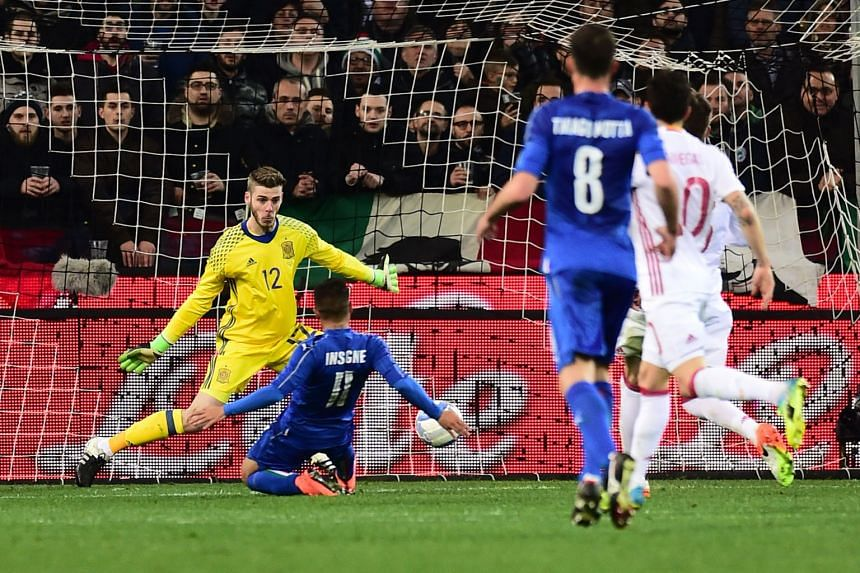 (Above )  Italy forward Lorenzo Insigne slides in to open the scoring past Spain's goalkeeper David de Gea during their teams' 1-1 draw at Udinese's Stadio Friuli.