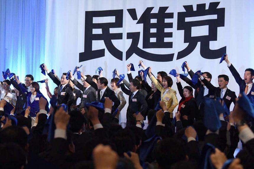 Parliament members of the main opposition Democratic Party wave blue handkerchiefs during the party's inauguration ceremony in Tokyo on March 27, 2016.