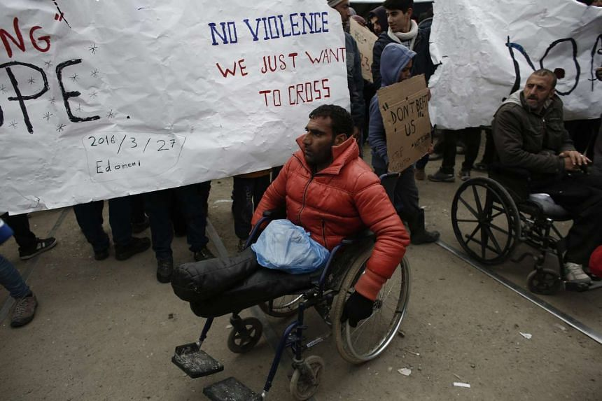 A disabled refugee takes part in a protest organised by refugees and migrants demanding the opening of the borders at the refugee camp of Idomeni near the Greek-Former Yugoslav Republic of Macedonia borders in northern Greece, on March 27, 2016.