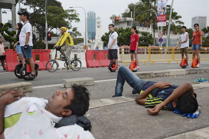 People on electronic unicycles ride pass sleeping workers along Esplanade Drive during Car-Free Sunday on March 27, 2016.