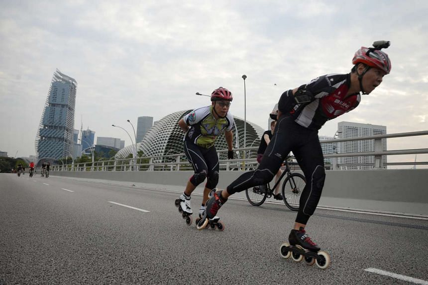 Two men speed skate down Esplanade Drive during Car-Free Sunday on March 27, 2016.