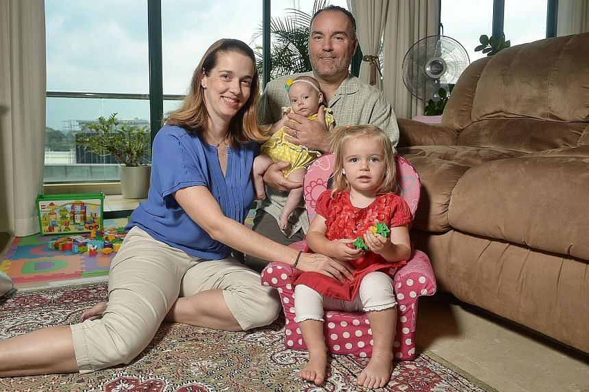 Mr Letzelter with his wife Jennifer and their daughters, three-month-old Lucy and 23-month-old Olivia. The couple find that it helps to stock up on clothes in the US during their visits home, as they can cost less there.