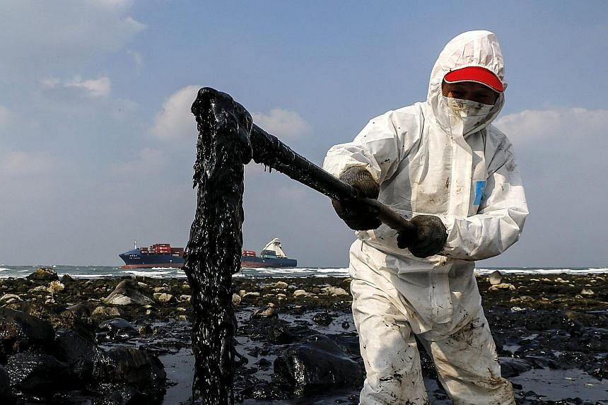 (Left) A worker collecting oil spilled from a container ship owned by T.S. Lines off Shimen, New Taipei City, Taiwan, yesterday. The 15,487-tonne ship ran aground in a storm about 300m from the shore while it was sailing from Hong Kong to Keelung Por