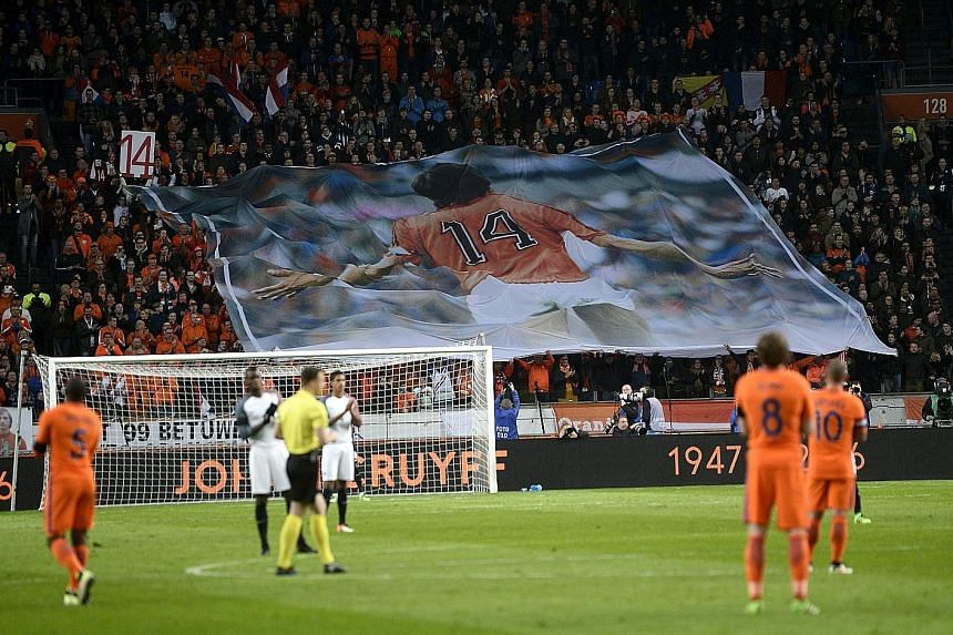 Players for the Netherlands and France teams stopped play during the 14th minute of their friendly match at Amsterdam ArenA on Friday to pay tribute to Johan Cruyff. The Dutch legend died on Thursday after a five-month battle with lung cancer.