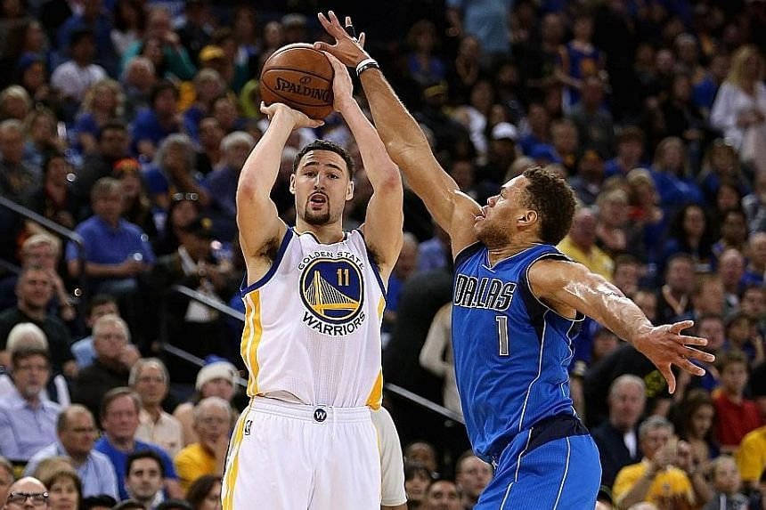 Golden State Warriors guard Klay Thompson (left) hits one of his nine three-pointers over Dallas Mavericks swingman Justin Anderson. The Warriors set an NBA record of most three-pointers in a season (938) with 10 games to go during their 128-120 win