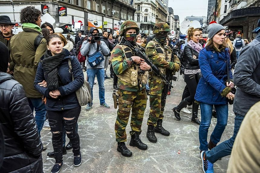 "Soldiers standing guard as people pay respects to victims of Brussels' bombings, which killed at least 31 people and injured about 300 more. Belgian Interior Minister Jan Jambon had gone on radio one day earlier and warned that his country faced a ""c"