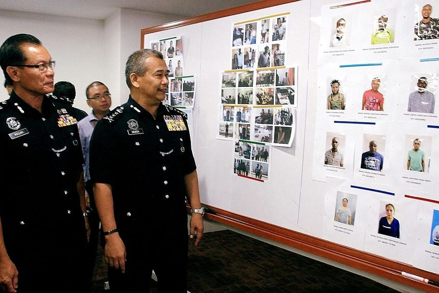 A Malaysian police press conference held last year, where photos of African suspects in love scams were displayed. There were 14,627 cases of online scams last year, in which victims lost a total of RM1.09 billion.