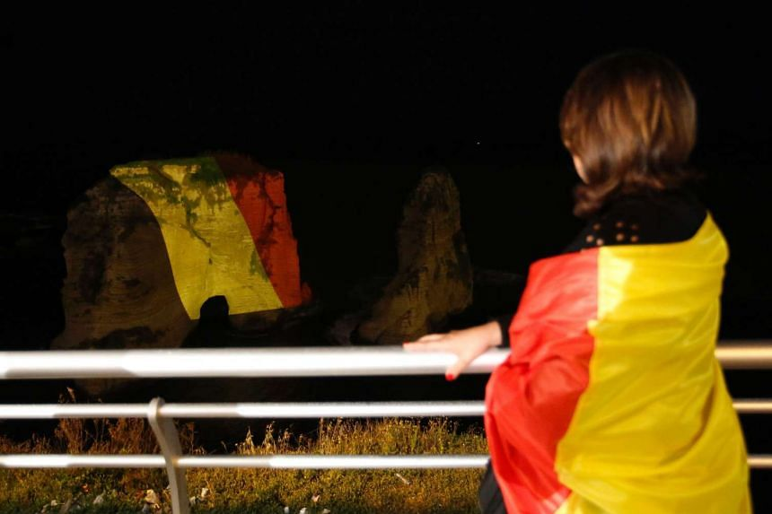 A woman looks at Beirut's landmark of Rawshe illuminated in the colours of the Belgium flag on March 26, 2016.