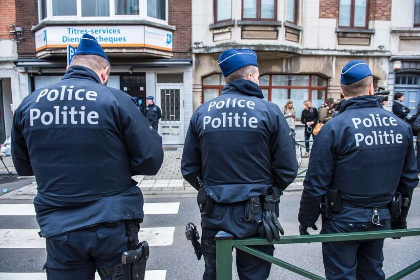 Police officers during an operation searching for suspects of the March 22 terrorist attacks in Brussels on March 25, 2016.