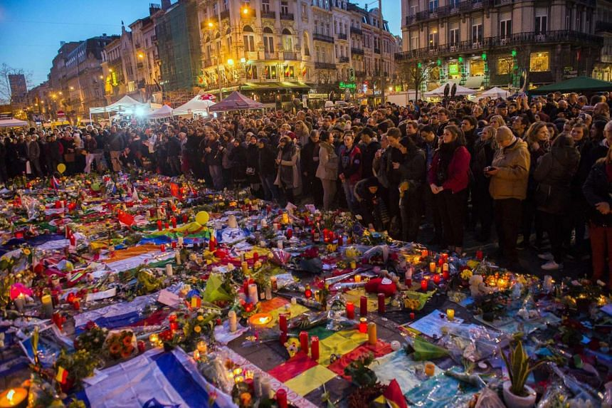 People gathering at a makeshift memorial in tribute to the victims of the Brussels terror attacks, on Place de la Bourse square in Brussels on March 25, 2016.