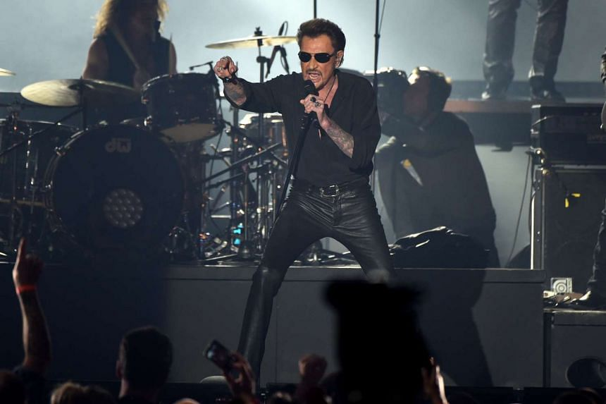 French singer Johnny Hallyday performs on stage at the beginning of his concert in Brussels, on March 26, 2016.