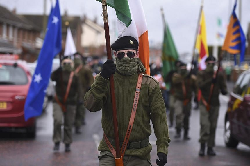 Masked members of Republican Sinn Fein commemorate the 100th anniversary of Easter Rising in Lurgan, Northern Ireland, on March 26, 2016.
