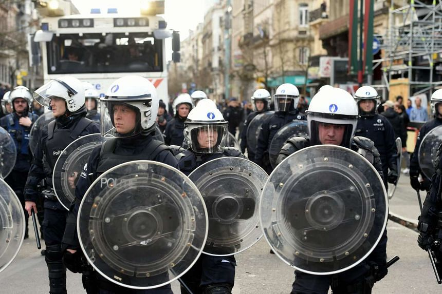 Riot police surround the makeshift memorial to victims of the Brussels attacks as nationalist demonstrators disturb the peaceful rally on Place de la Bourse square in Brussels on March 27, 2016.