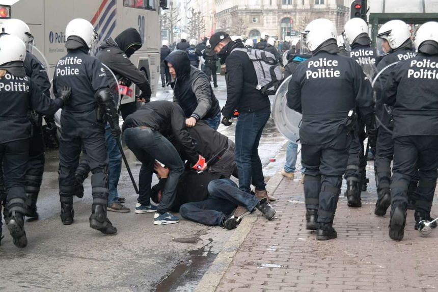 A rioter is arrested by the police.