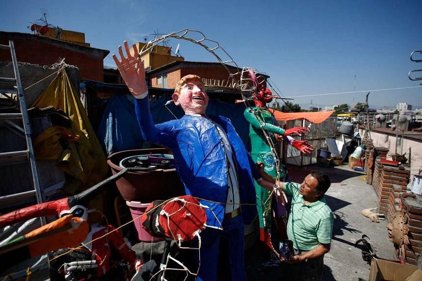 Craftsman Felipe Linares puts the final touch to an effigy depicting Republican US  presidential candidate Donald Trump in Mexico, on March 25, 2016.