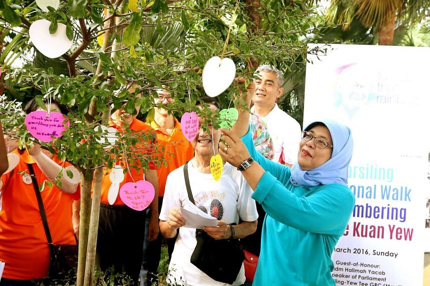 Madam Halimah Yacob hanging a note on a tree at Bay East Garden during a memorial event for former prime minister Lee Kuan Yew.