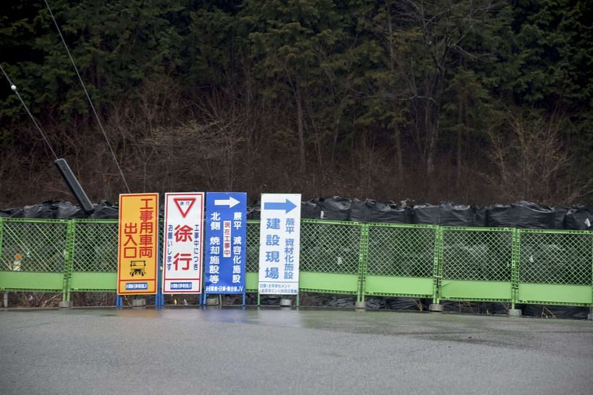 Black bags containing contaminated soil are seen all over the village.