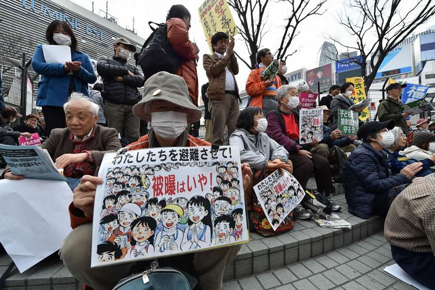 Demonstrators display placards calling on the government to protect children against radiation during an anti-nuclear protest in Tokyo on March 5, 2016.